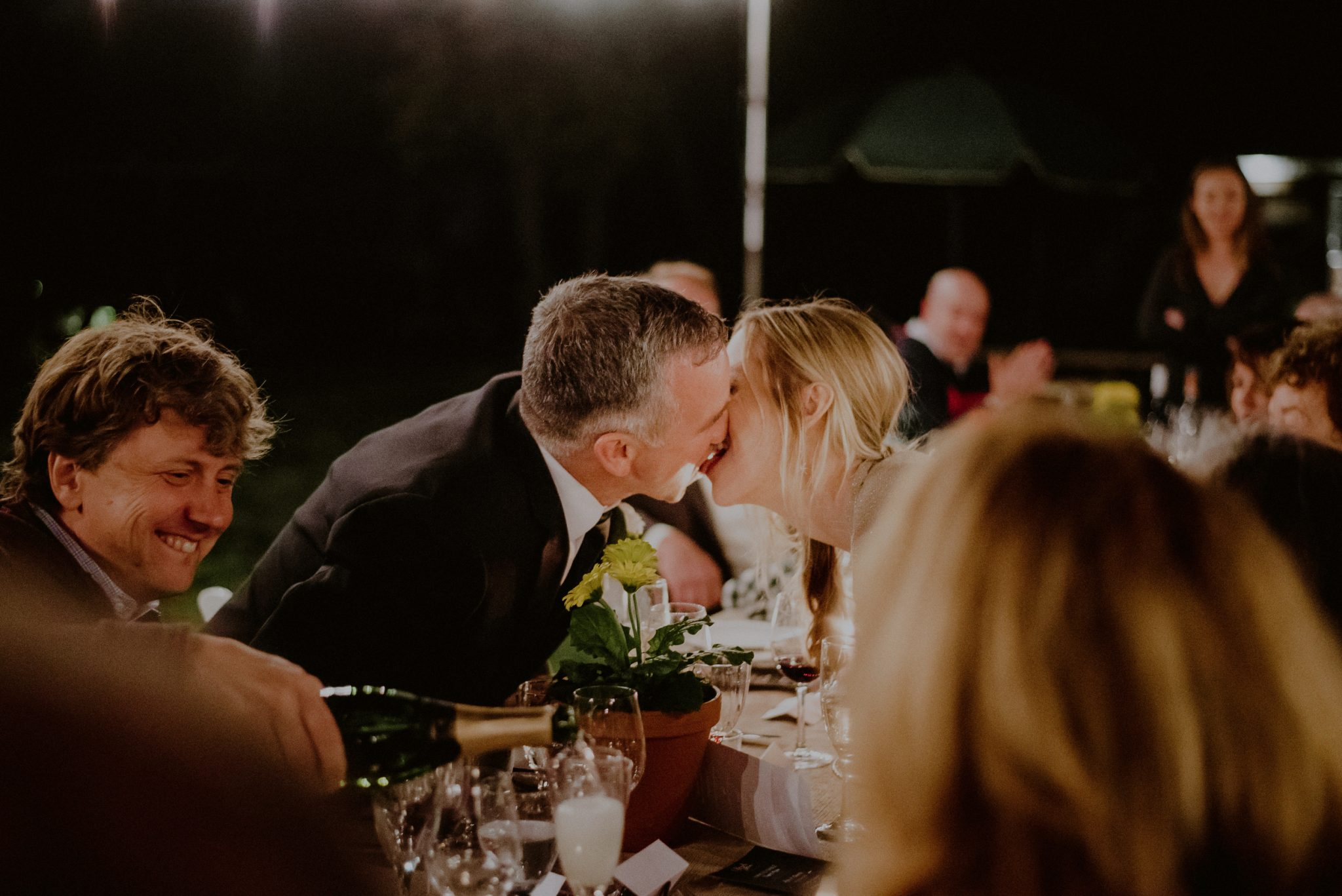 candid kiss between bride and groom during dinner