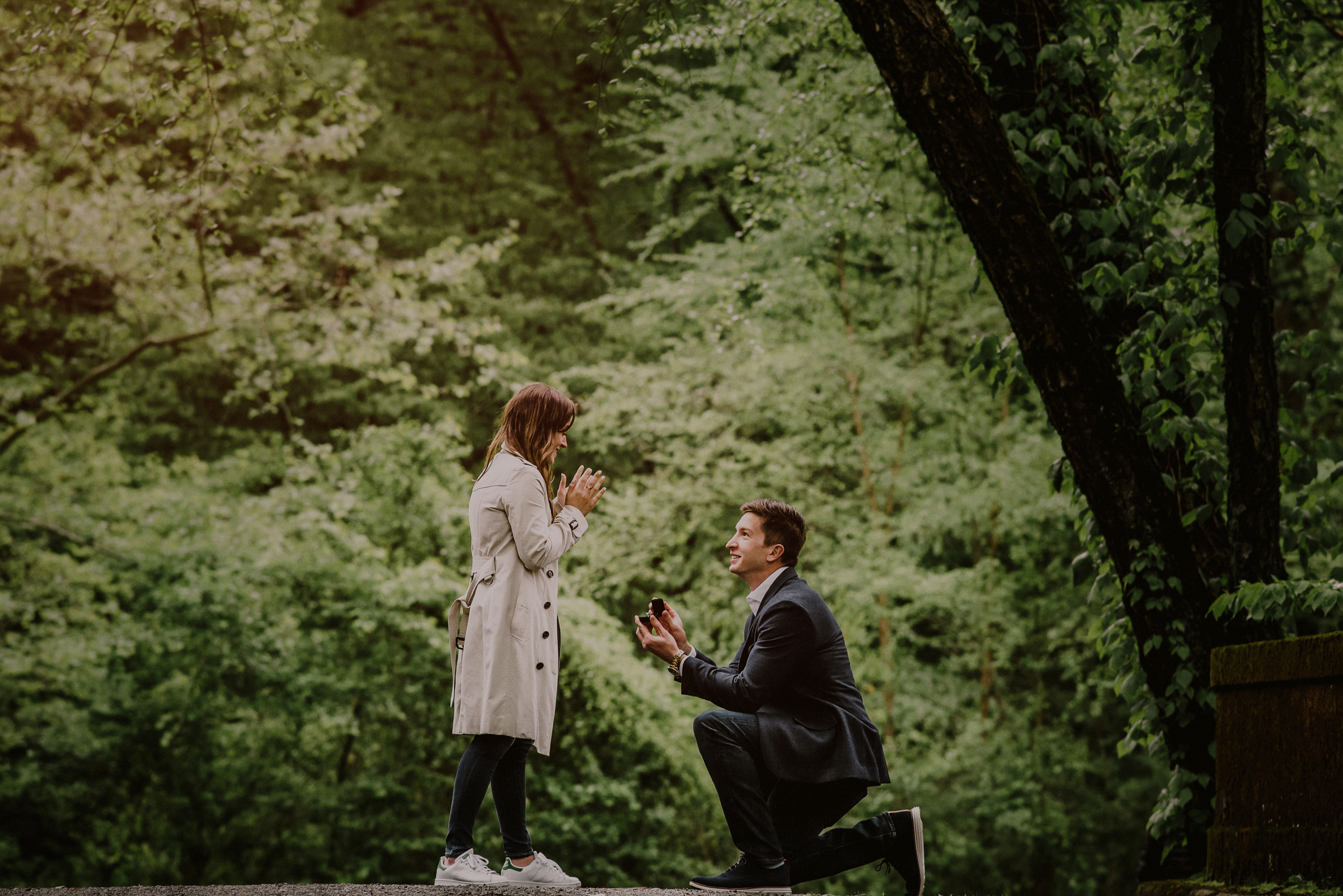 man on his knees proposing in woods