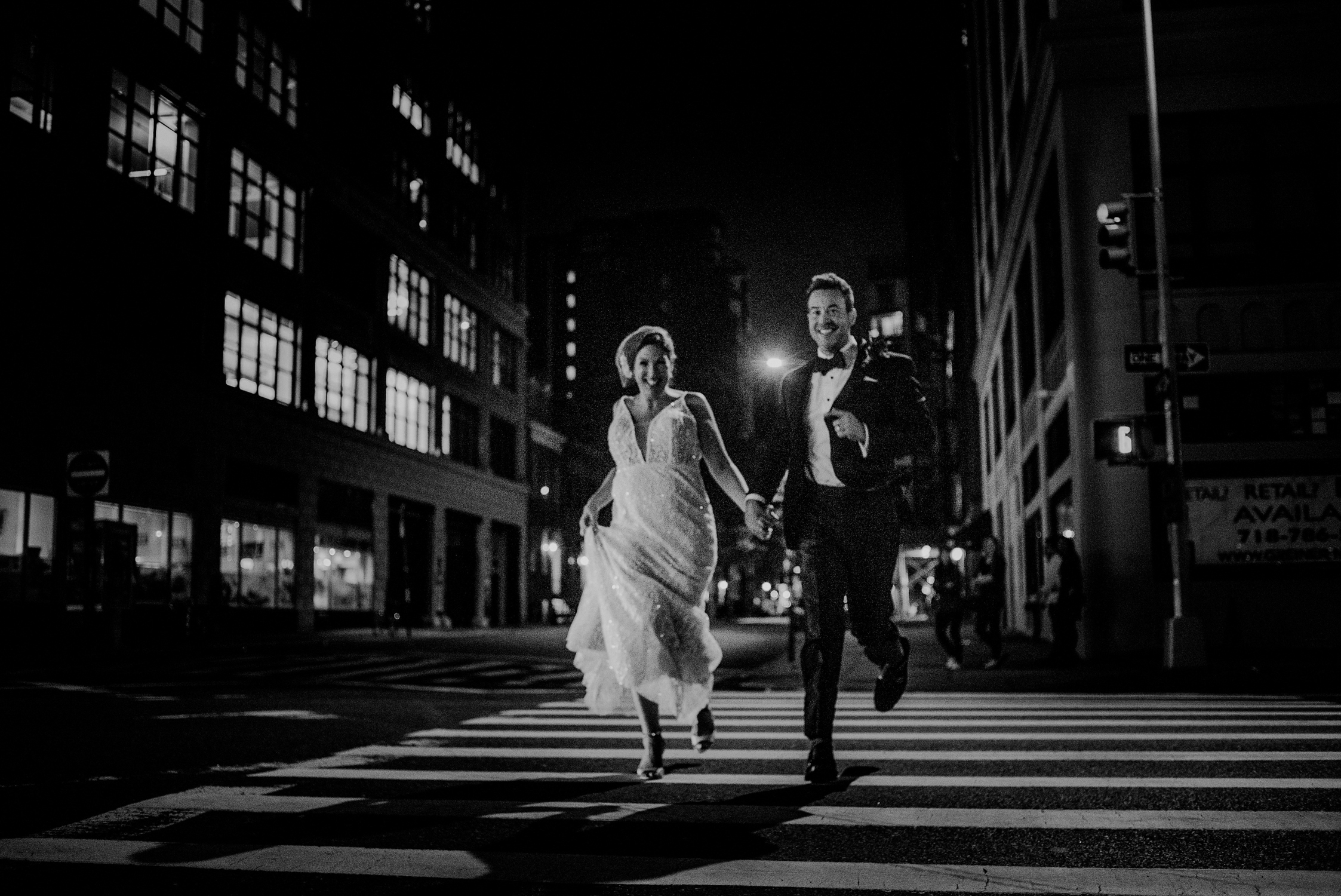 happy couple running through streets of nyc in wedding attire